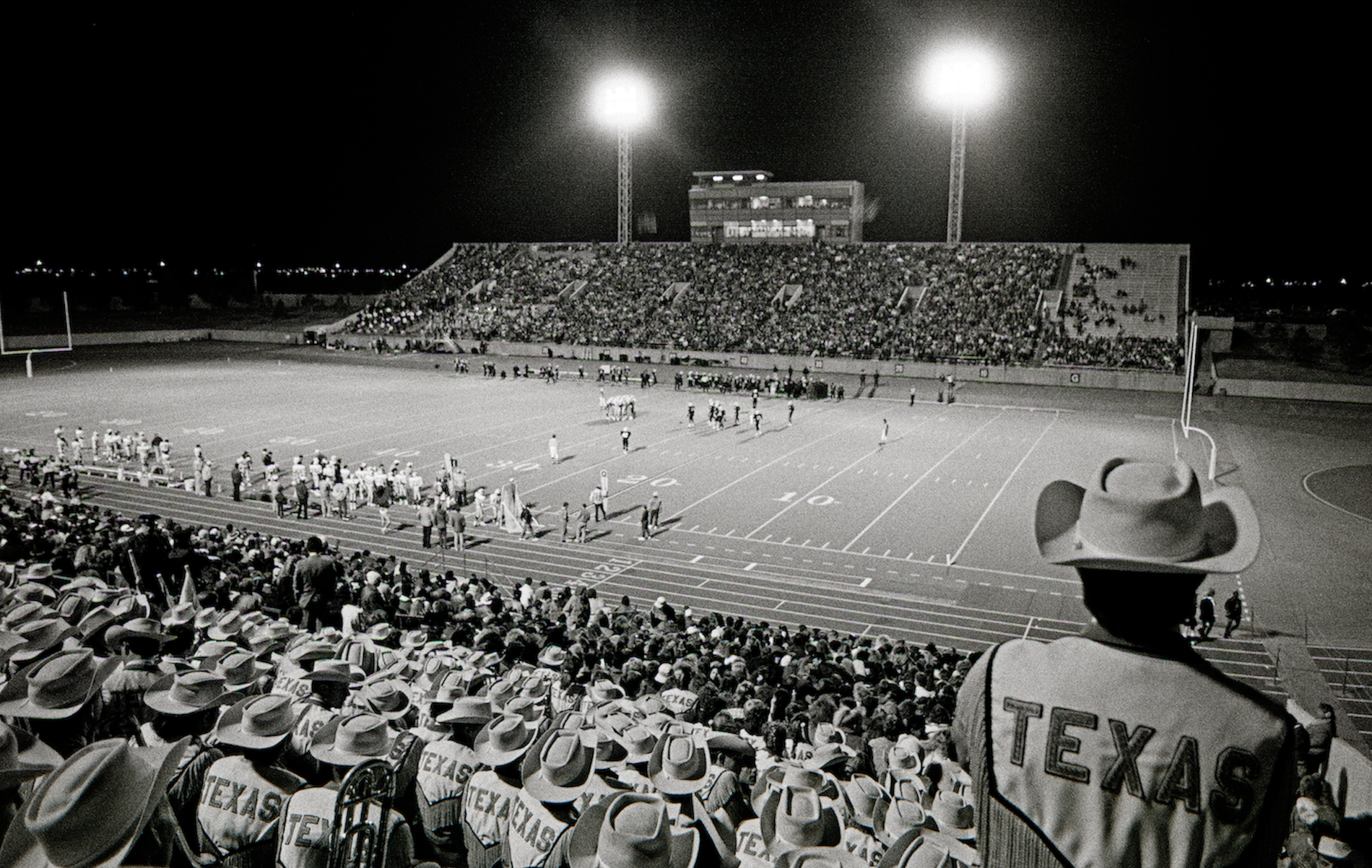 Black-and-white stadium scene with players on the field and an audience