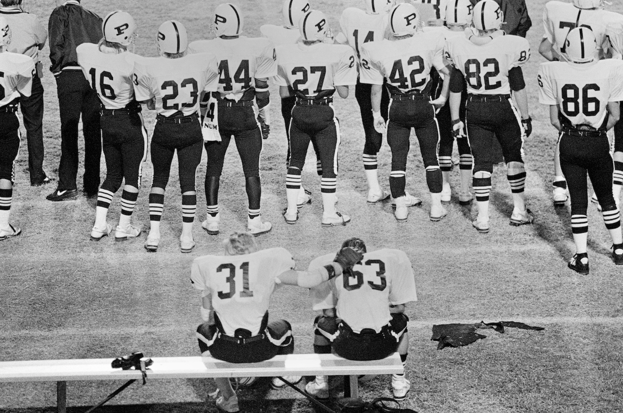 Two players sit on the bench as a number of other players stand on the field