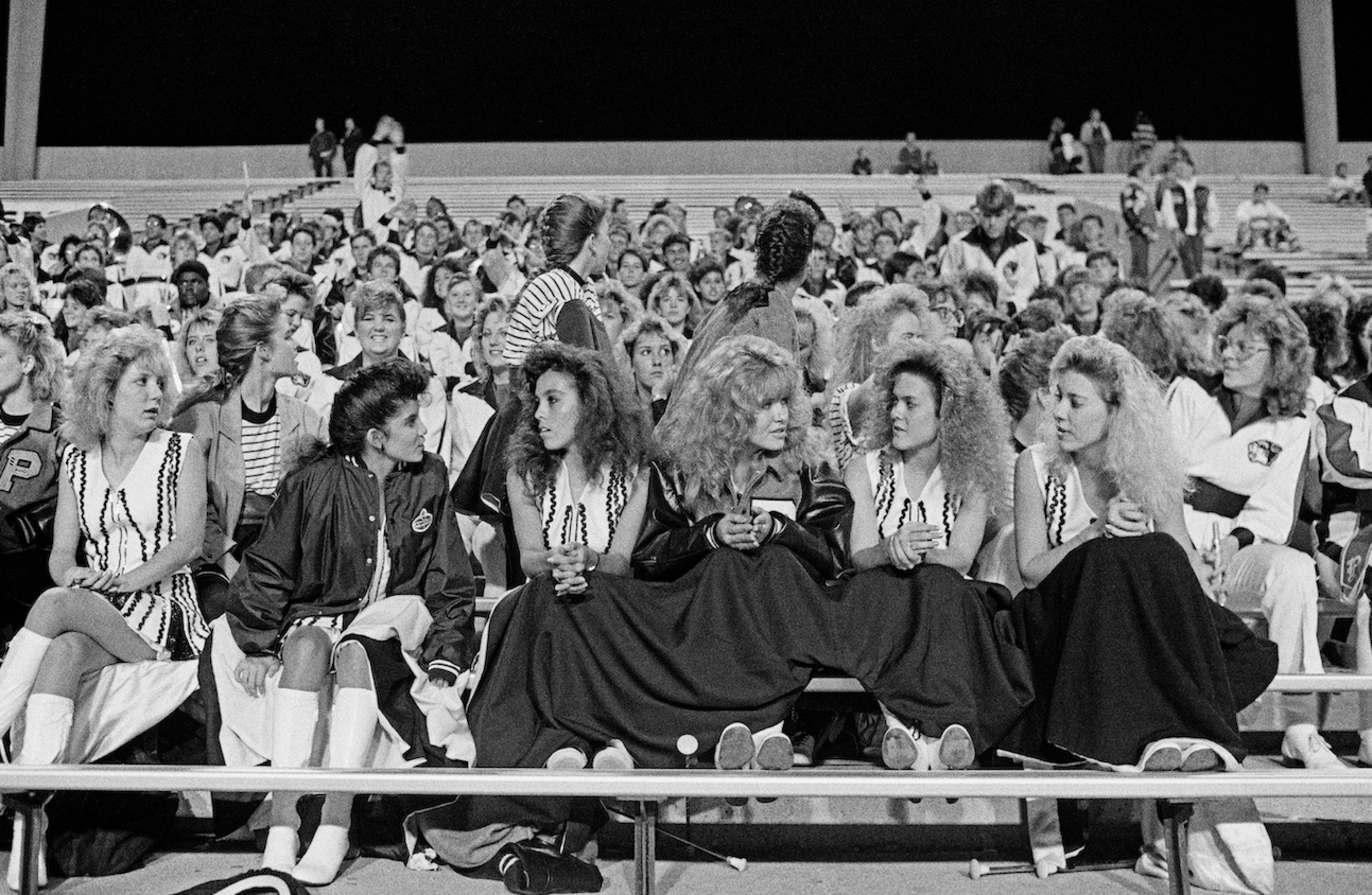 A row of cheerleaders sit on a bench with a crowd behind them