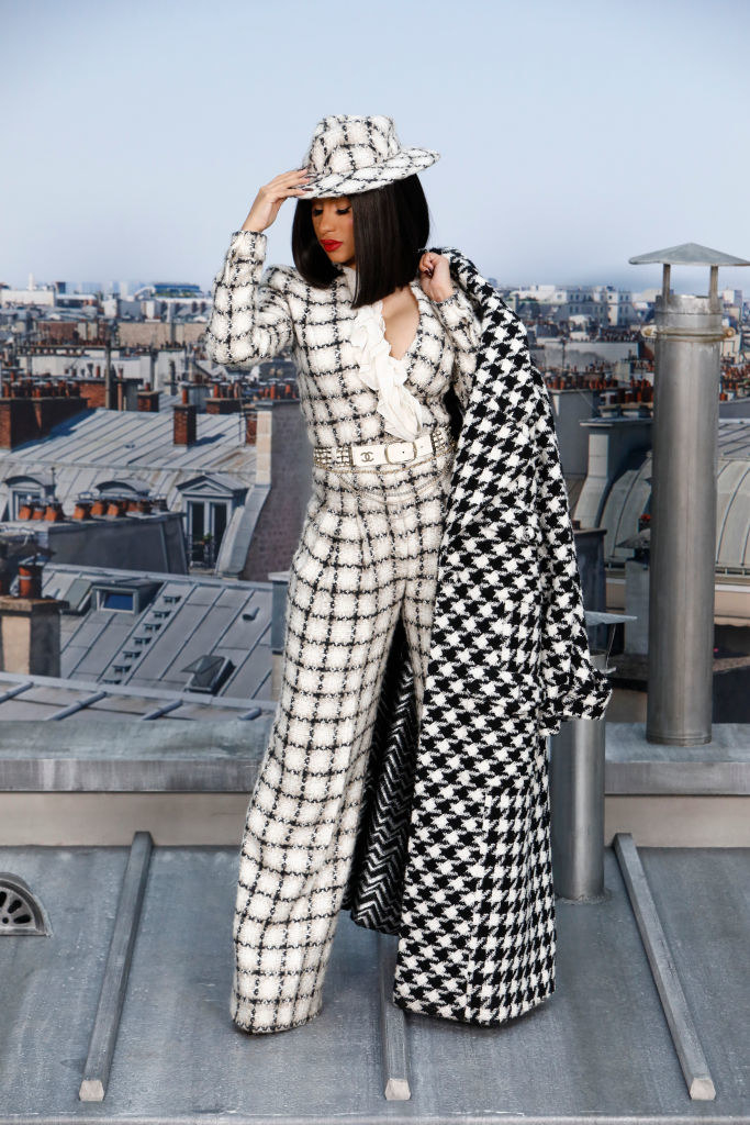 Cardi is wearing a checkered tweed pantsuit with a matching fedora and a houndstooth coat