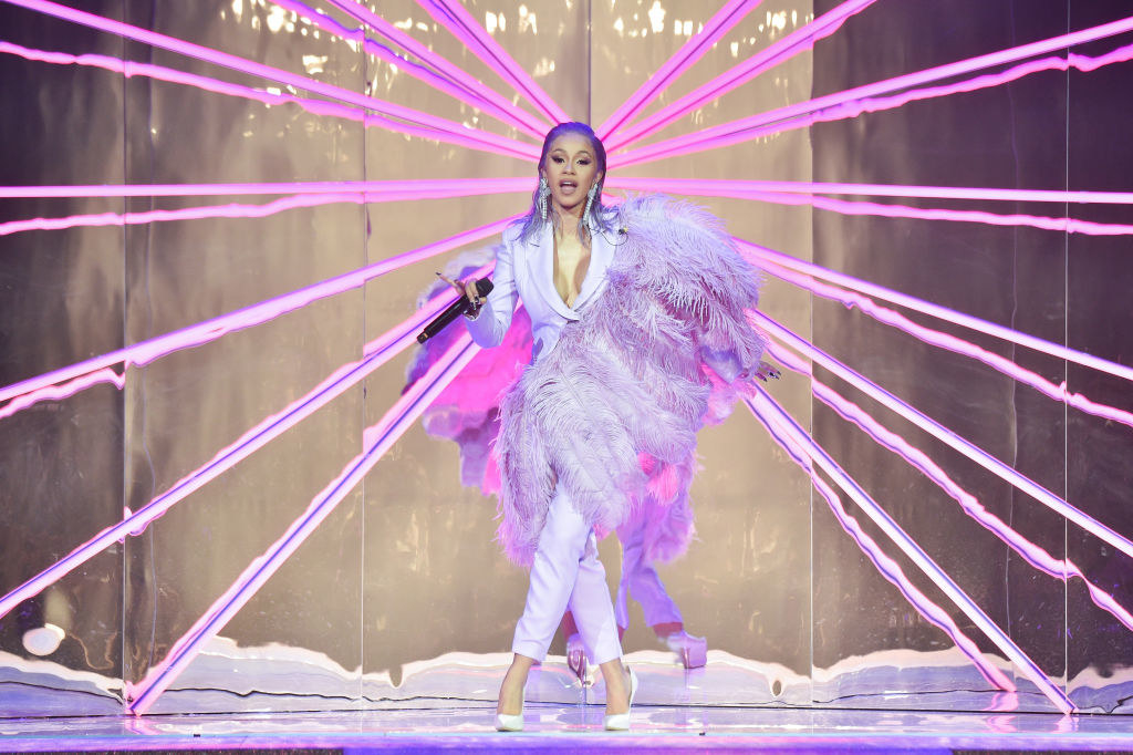 Cardi performing in a light-colored pantsuit with large feathers coming across her body