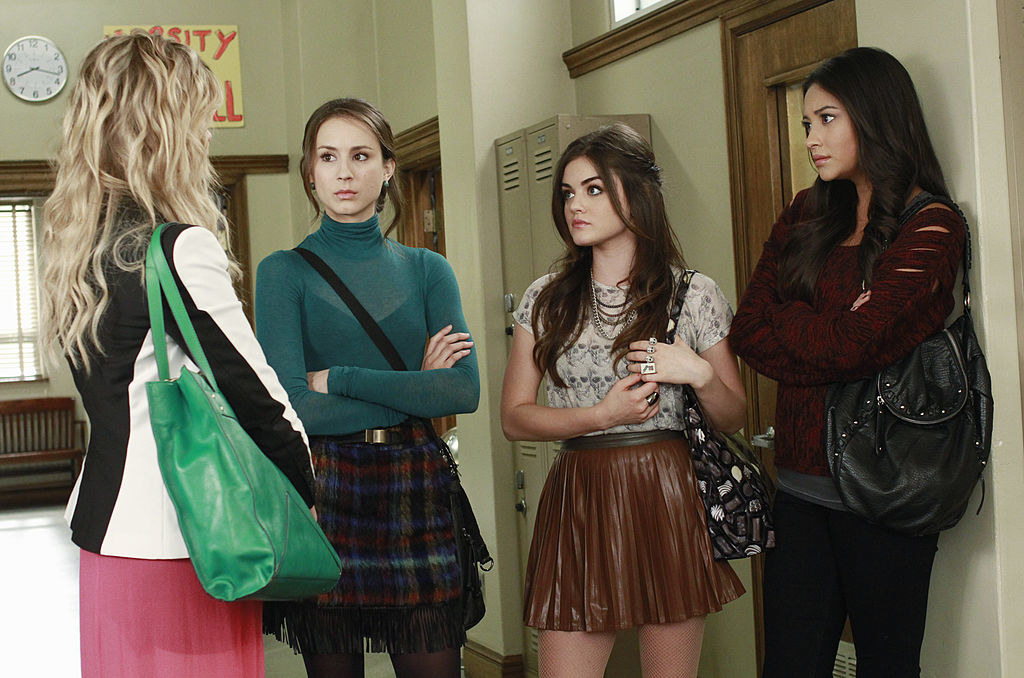 Aria wearing a brown bright skirt and a shirt with skulls on it