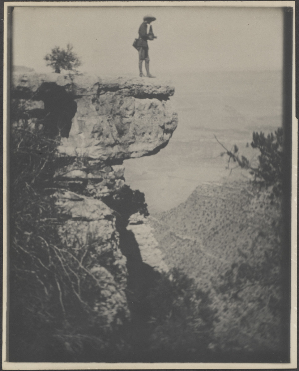 A person in a hat stands on a steep ledge overlooking the Grand Canyon, holding a camera