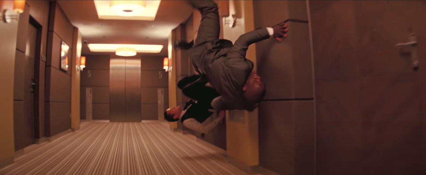 Arthur kicks off the wall as the hallway turns