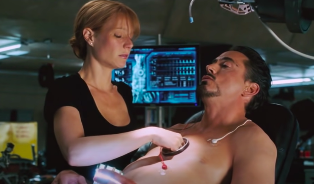 Pepper reaches into the hole in Tony's chest and pulls out the old arc reactor