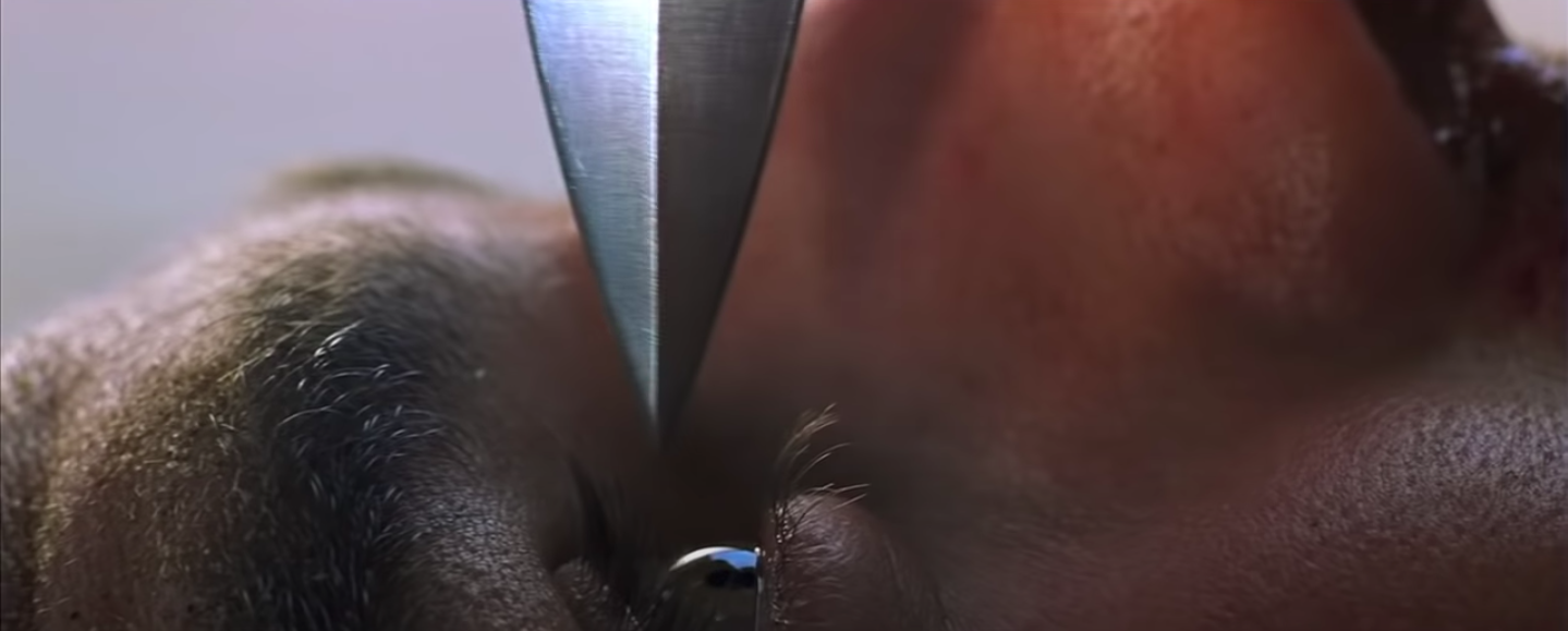 the tip of the knife is so close to Ethan's eyeball that it could trim his eyelashes