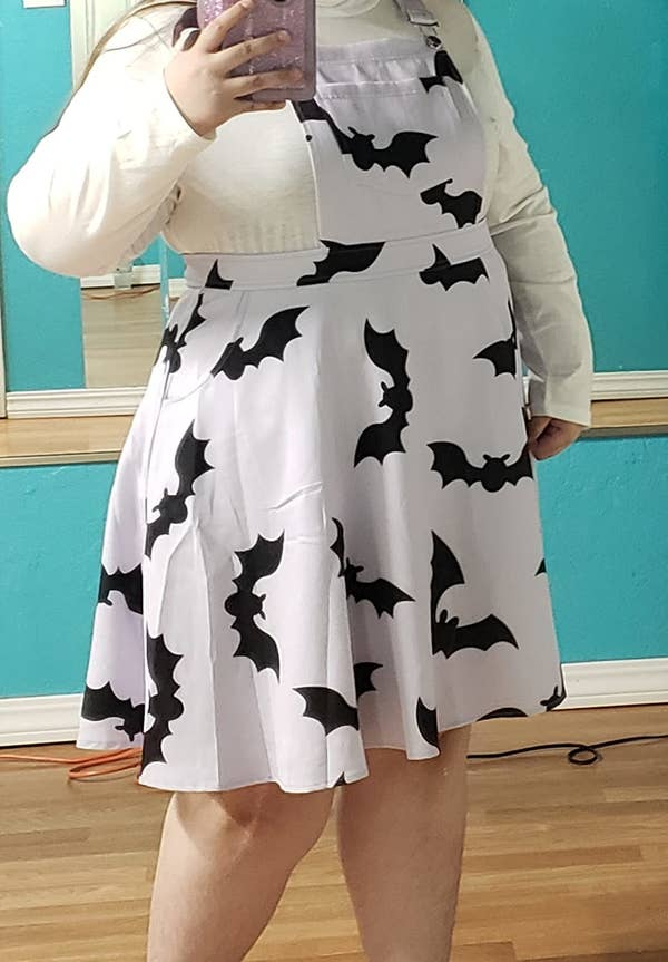 reviewer wearing the lilac bat-covered dress in a size 3X