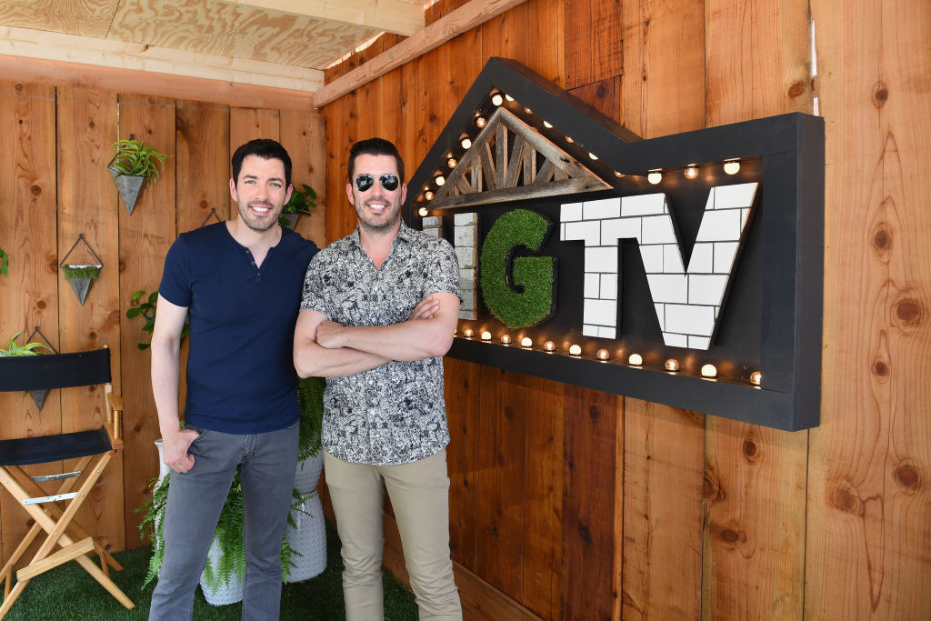 The Property Brothers pose next to HGTV sign