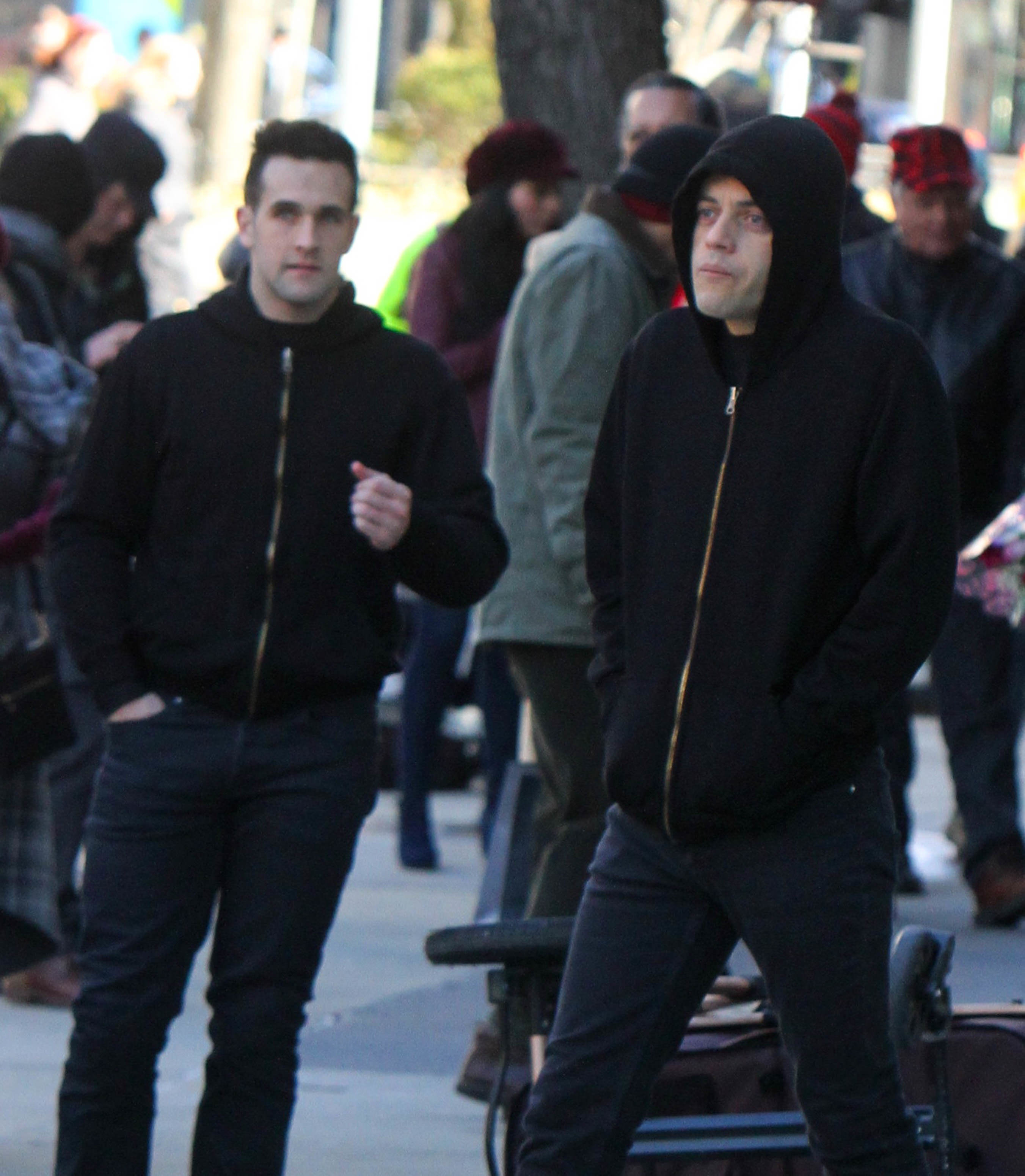 Rami Malek and his stunt double wearing black hoodies while filming
