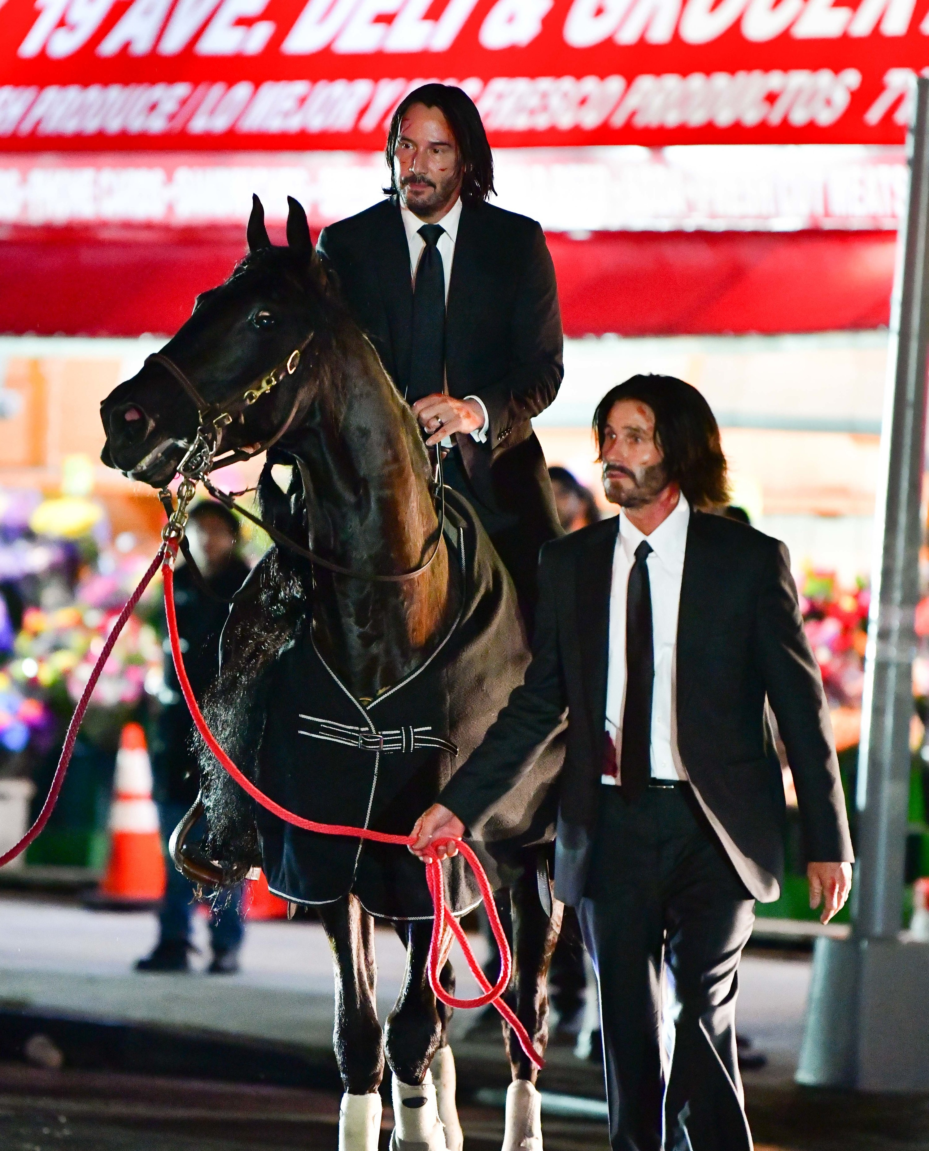 Keanu Reeves and his stunt double walking outside at night