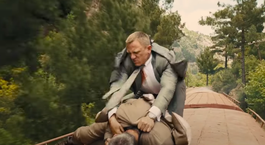 Bond holds Patrice down on the roof of the speeding train