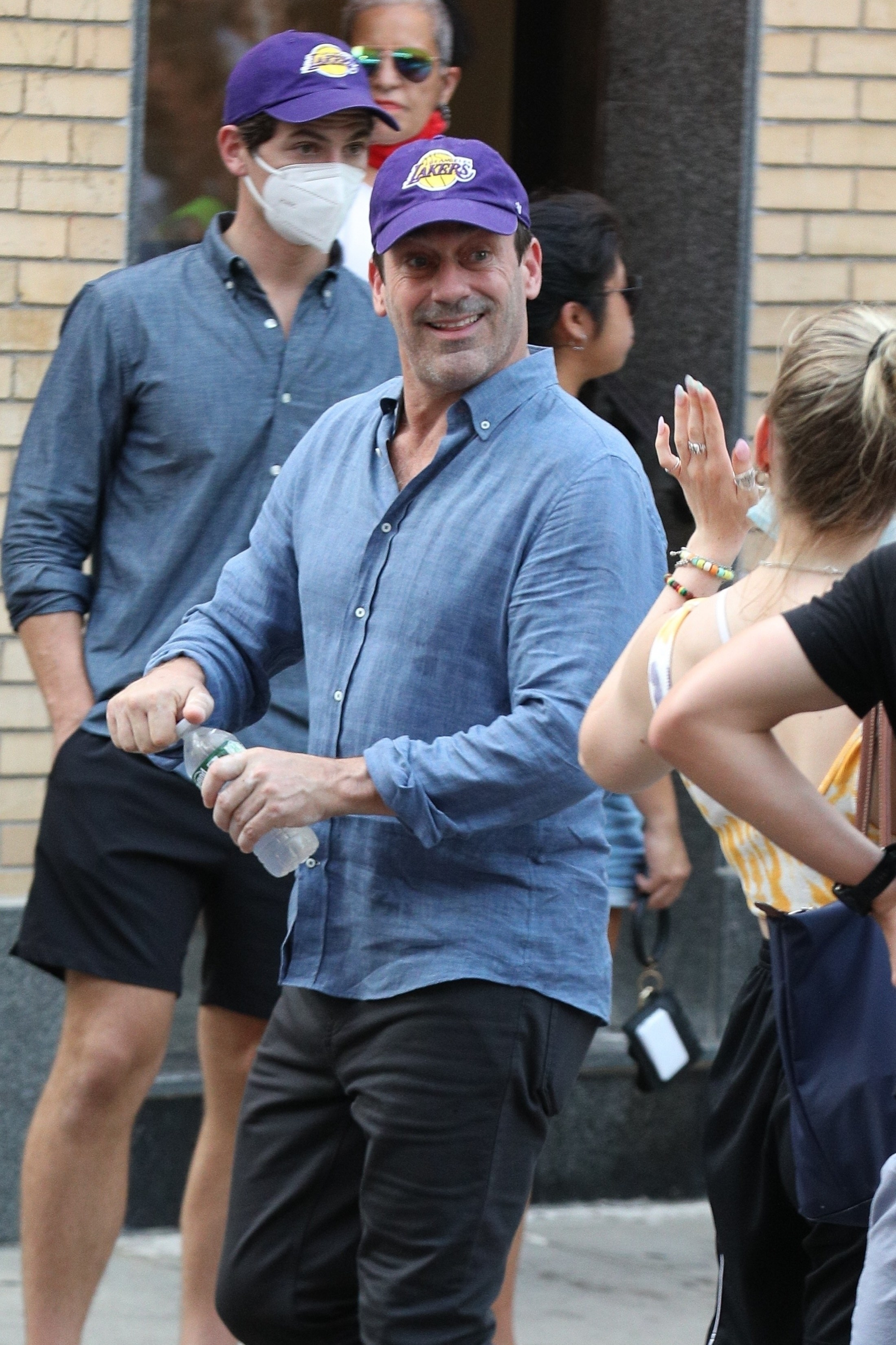 Jon Hamm and his stunt double wearing a lakers hat while filming