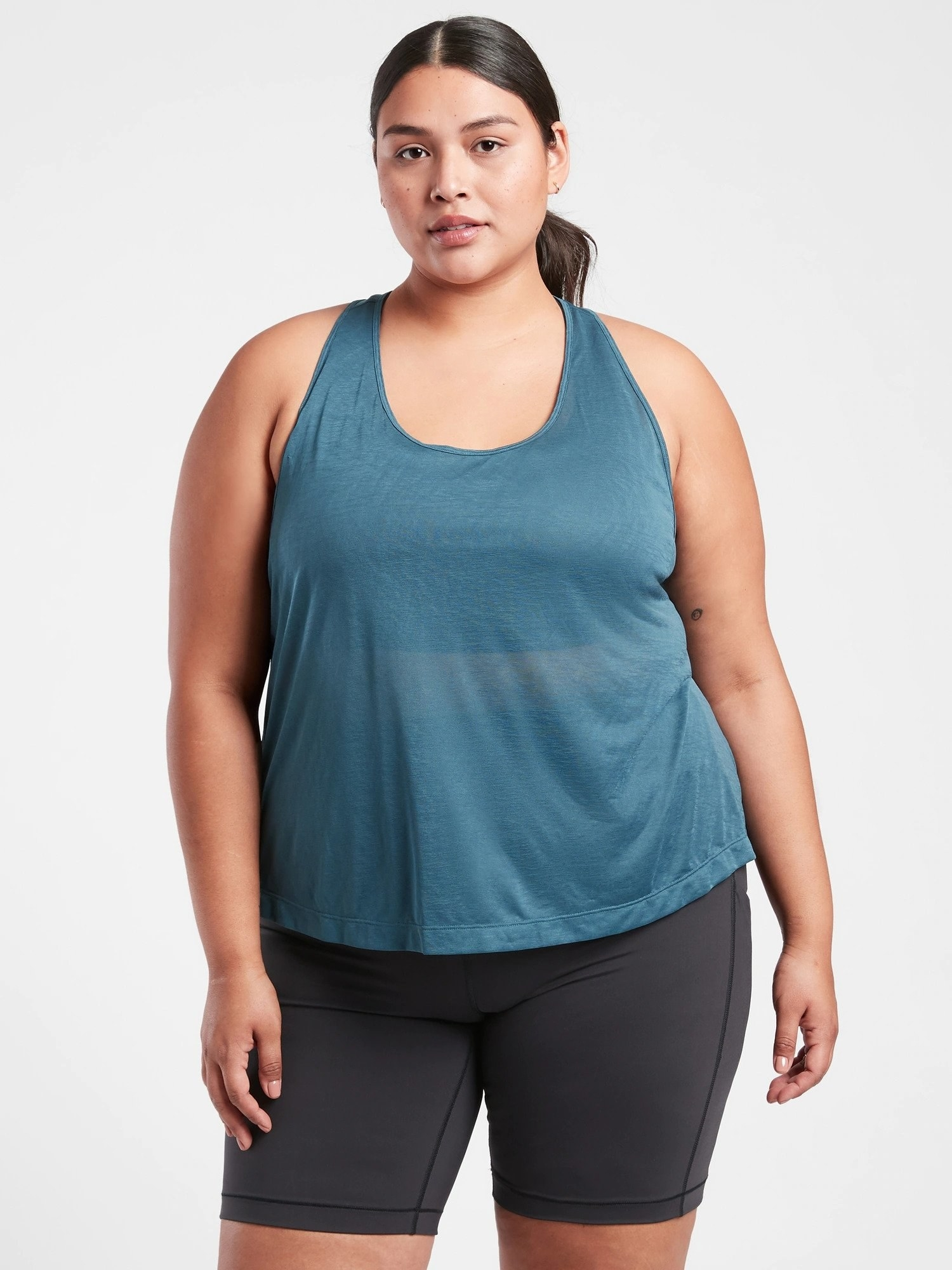 model in flowy, almost-sheer blue workout tank and leggings