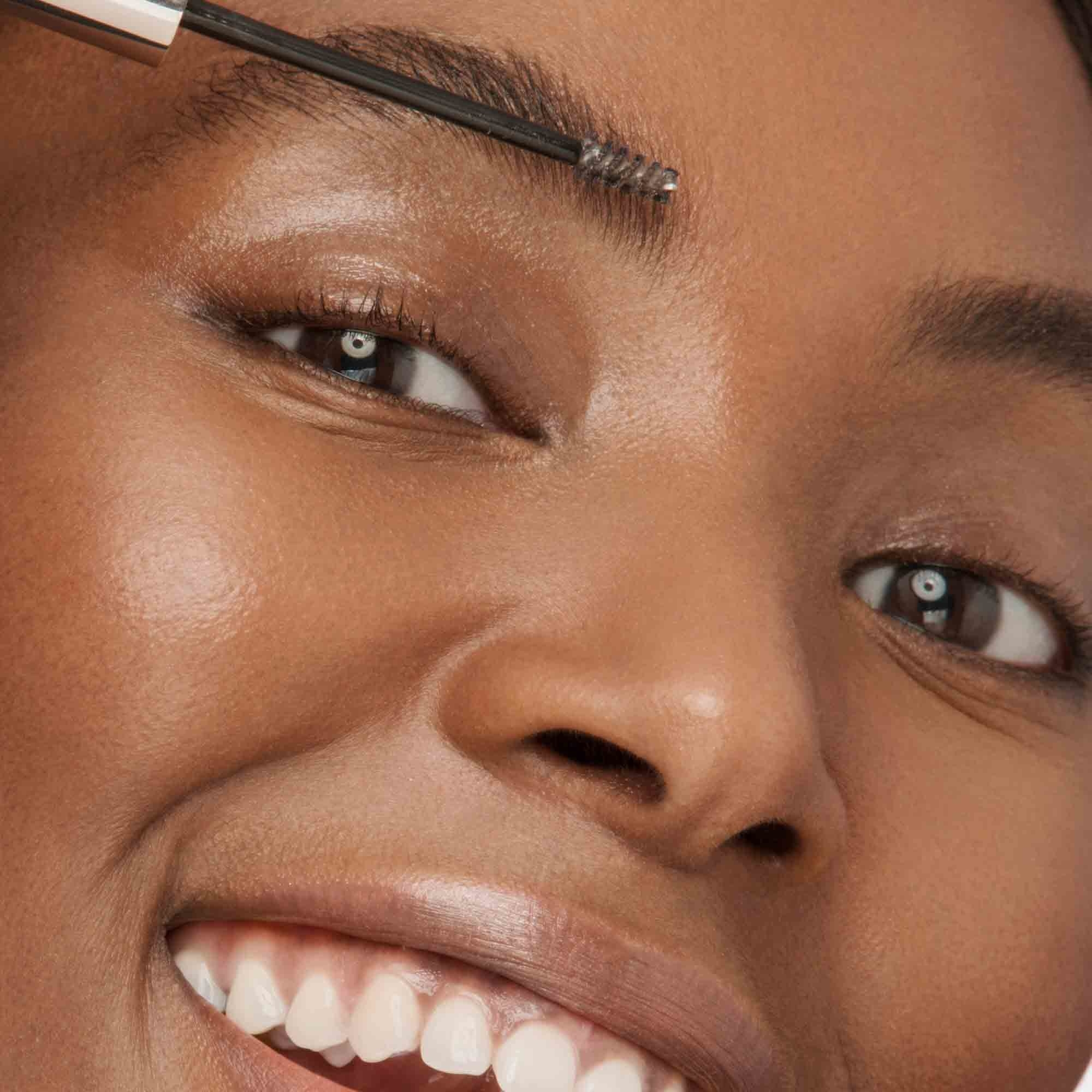 Woman applying Arch-ology Tinted Eyebrow Sculpting Gel on face