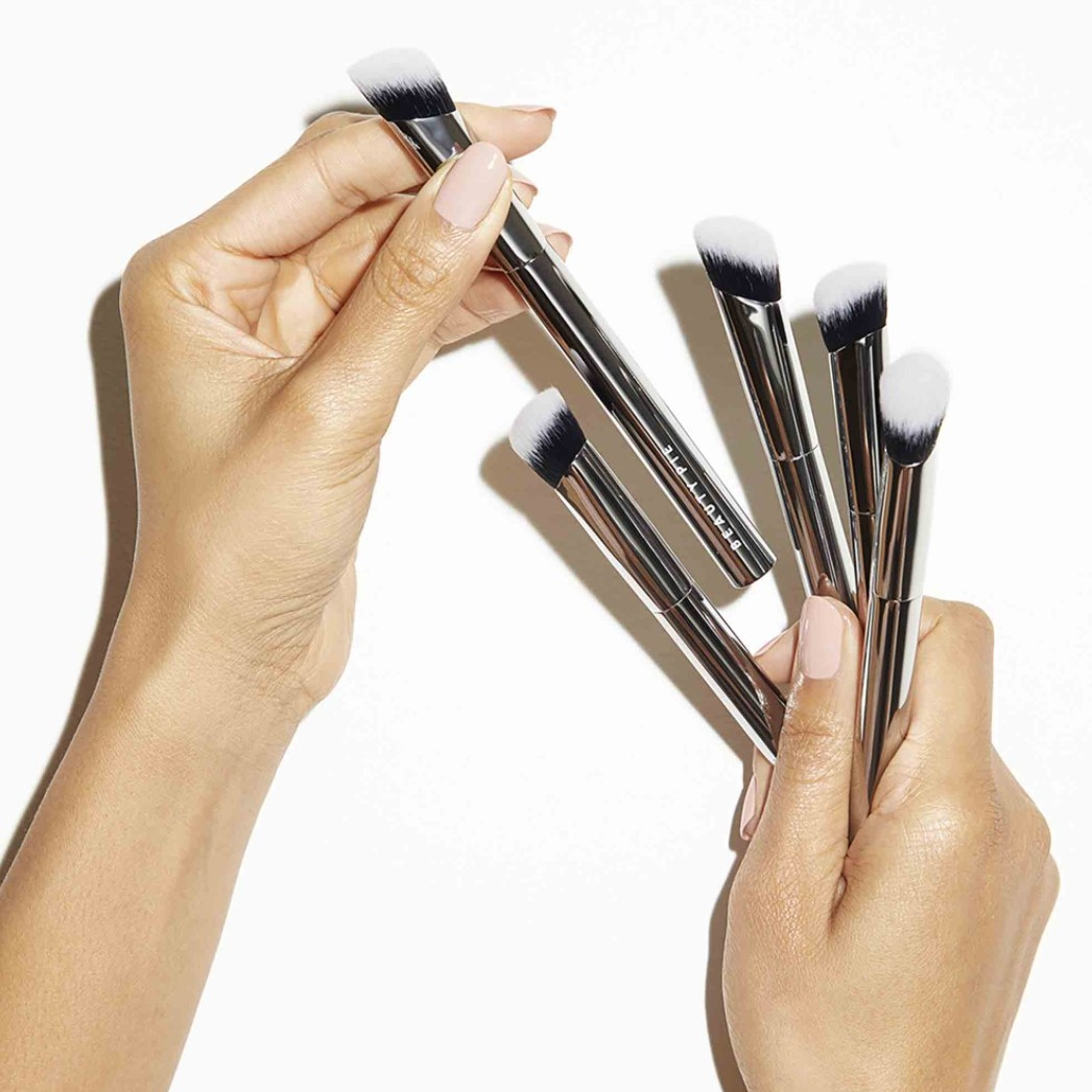 Woman holding several Pro Angled Concealer Brushes