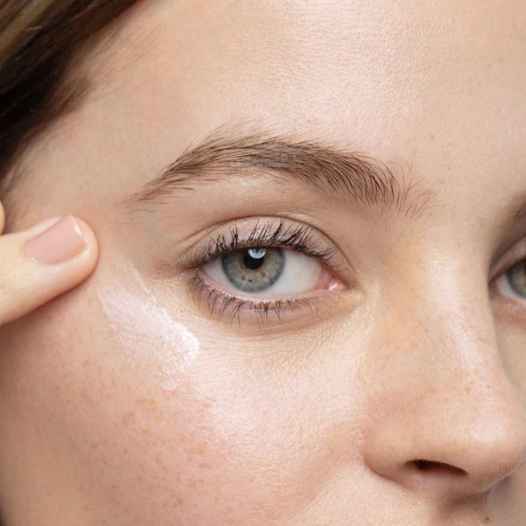 Woman applying WonderFilter Brightening Primer on cheek bones
