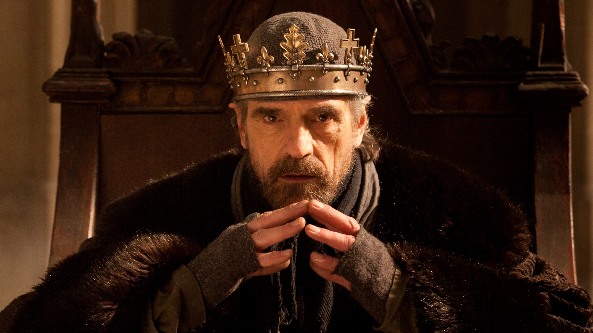 King Henry IV sitting on the throne while wearing his crown