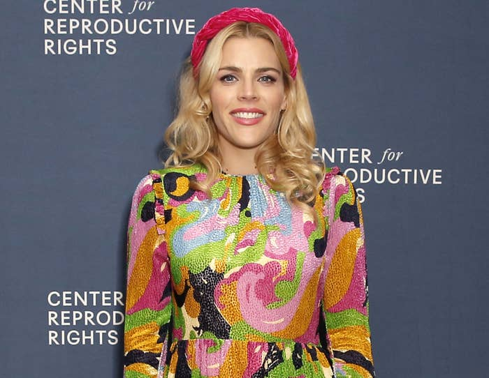 Busy wears a pink headband and colorful long sleeve dress to an event