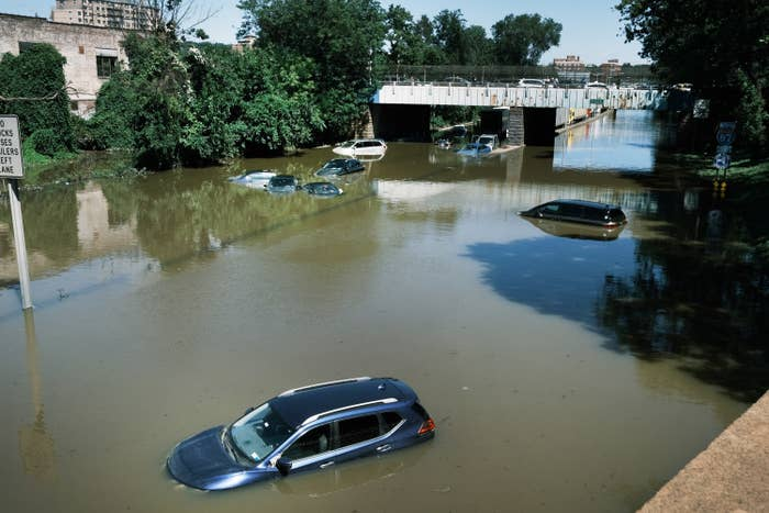 Cars are shown submerged by water on a flooded highway