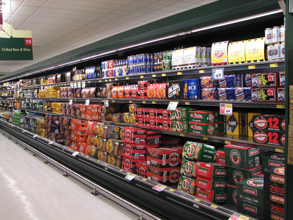 Cans of beer and wine being sold in a supermarket aisle