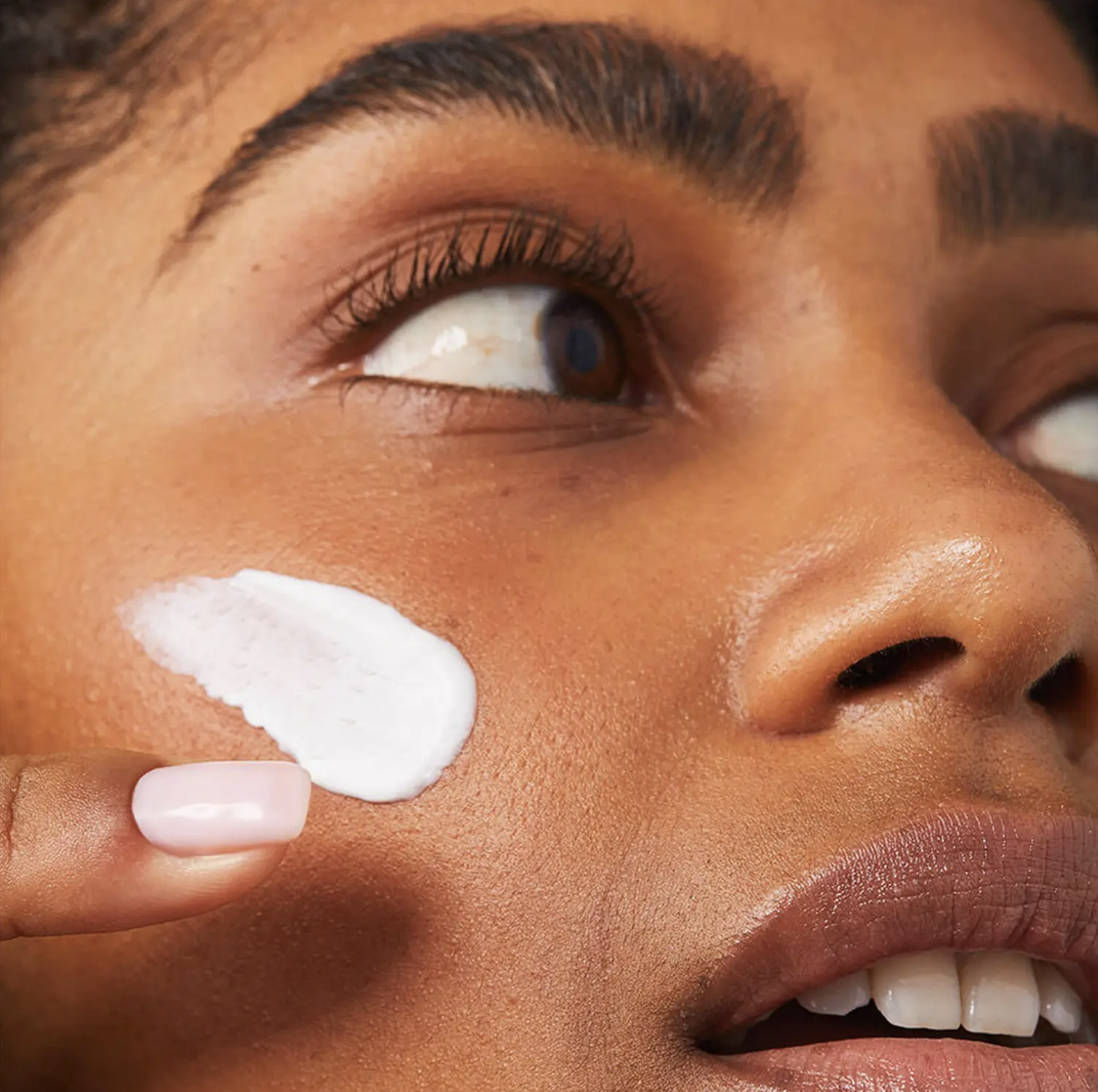 A person with a swipe of cream on their face