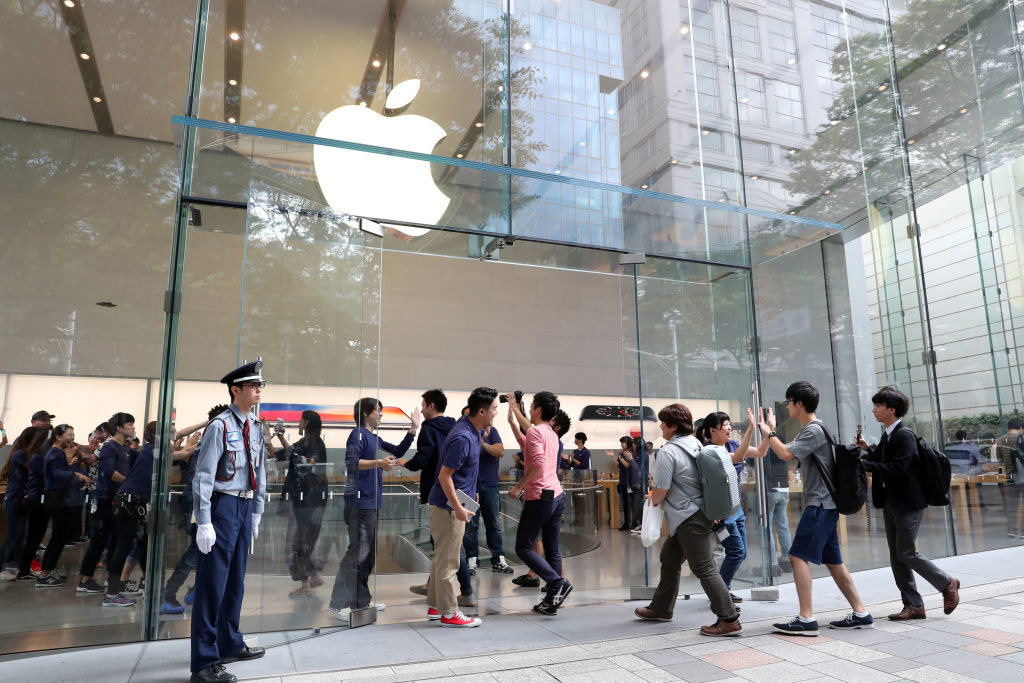 People going into a large apple store