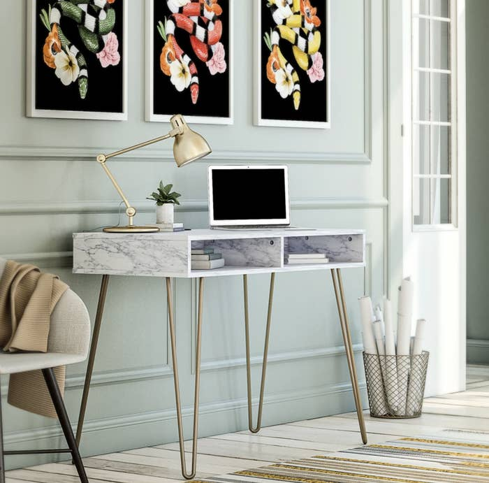 a marbled desk with gold hairpin legs