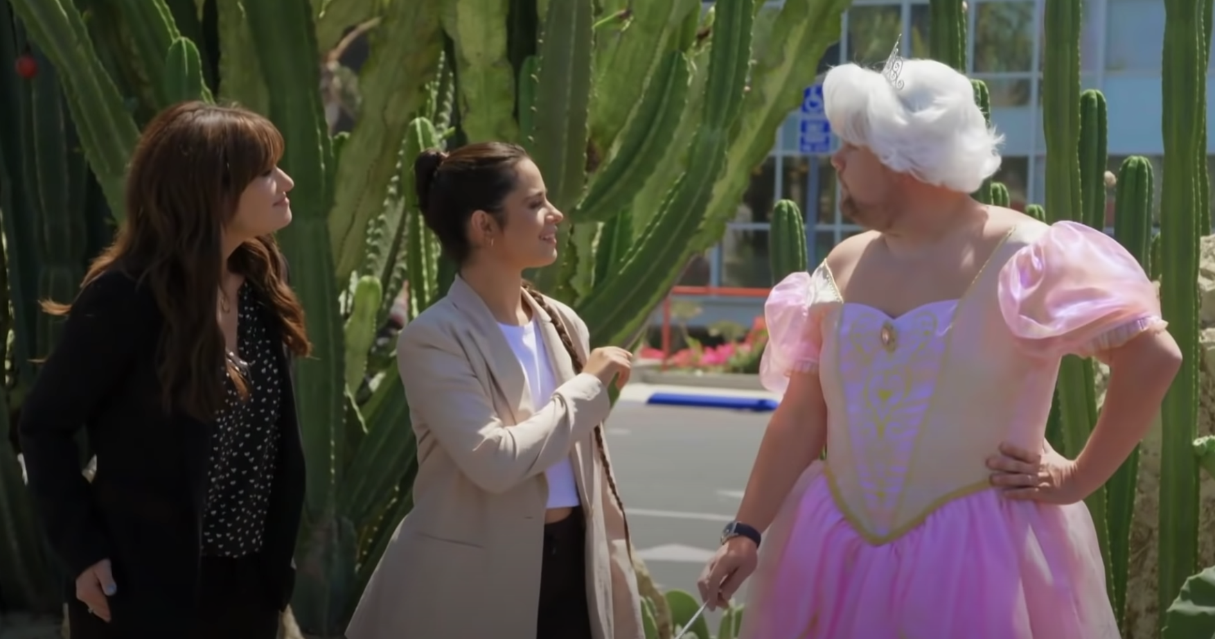 Idina, Camila, and James as the Fairy Godmother wearing a pink frilly dress