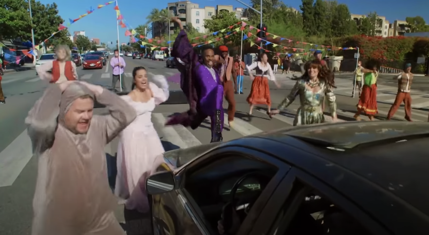 The cast performing in the crosswalk in front of a car