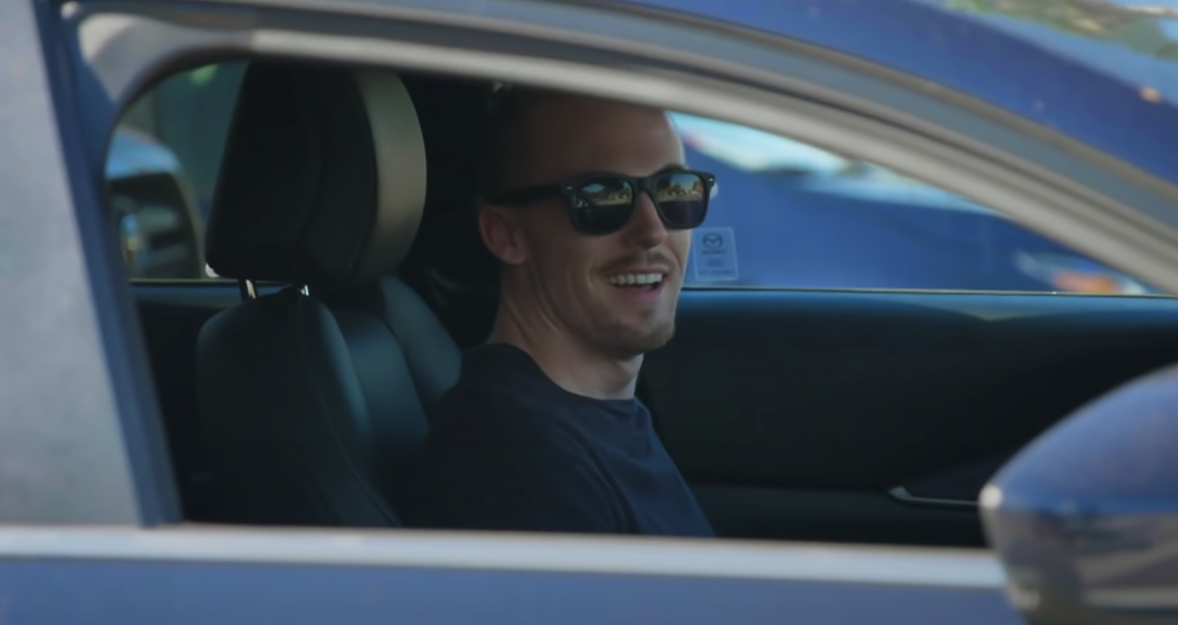 Smiling man wearing sunglasses sits in the driver's seat and looks at the camera