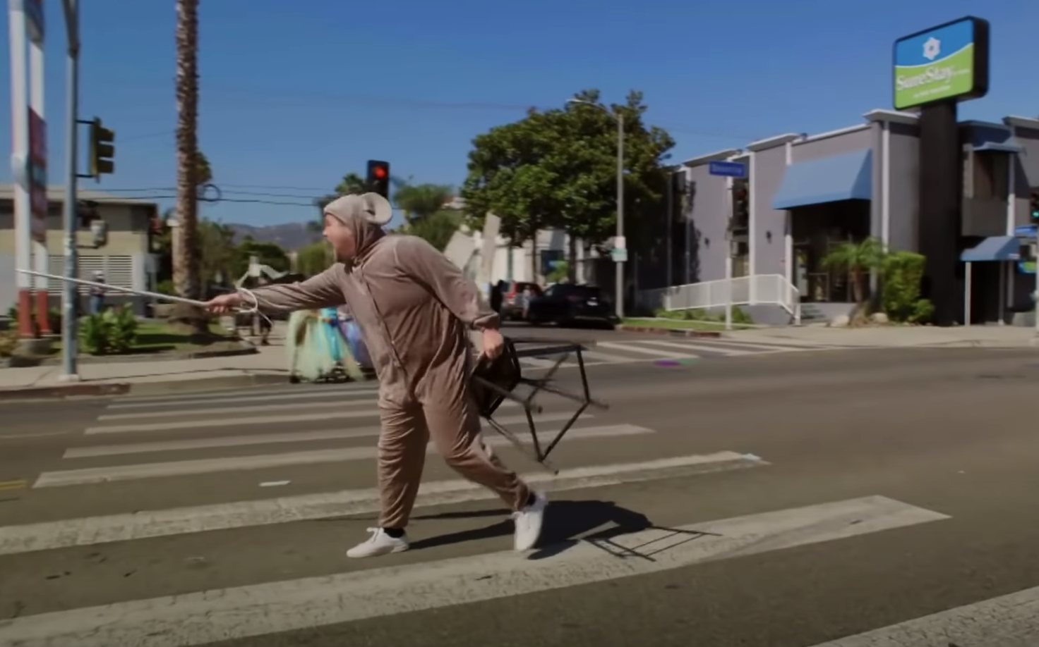 James dressed as a mouse standing in the crosswalk and holding a chair