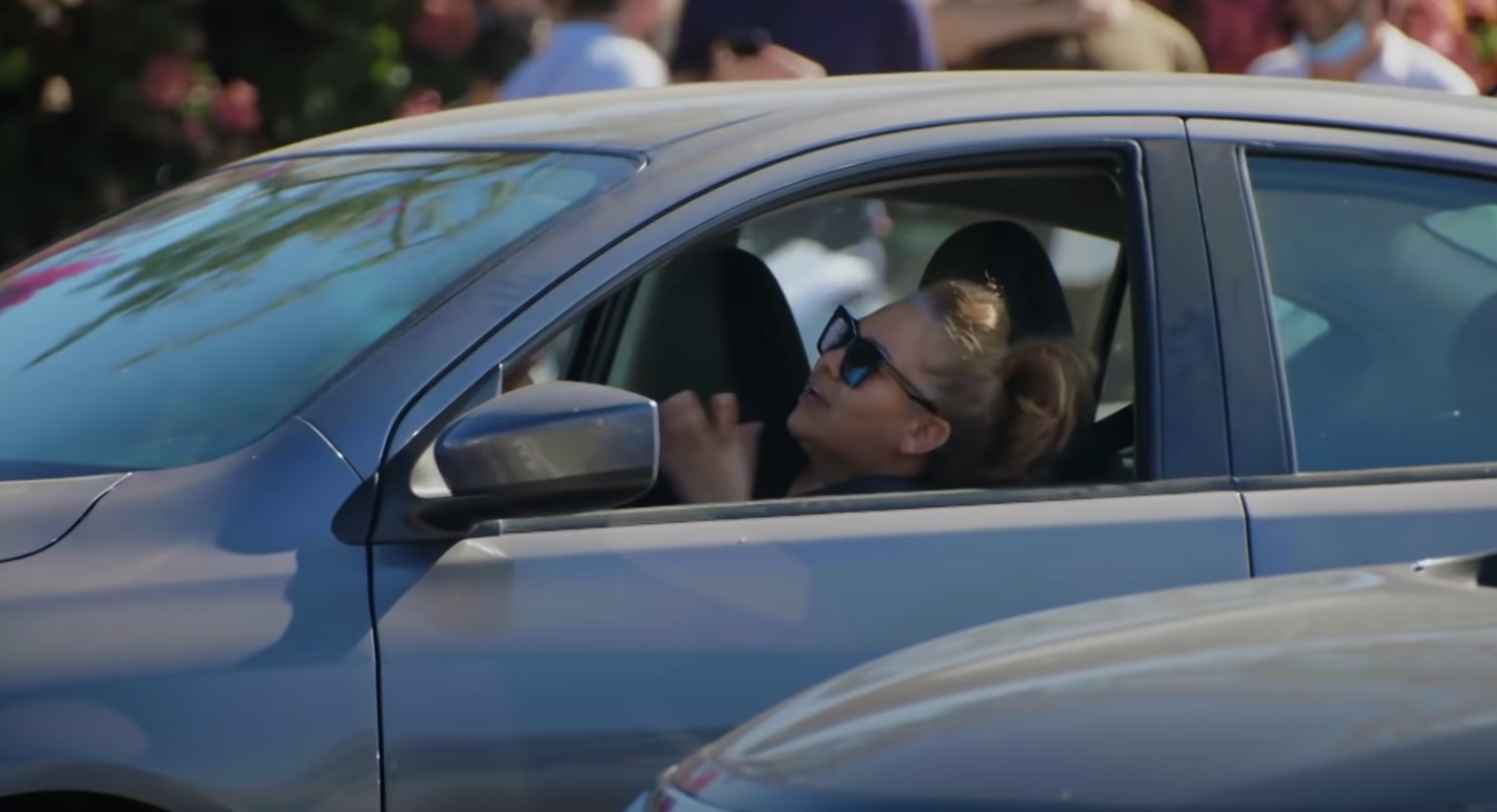Woman wearing sunglasses and sitting in the driver's seat looking frustrated