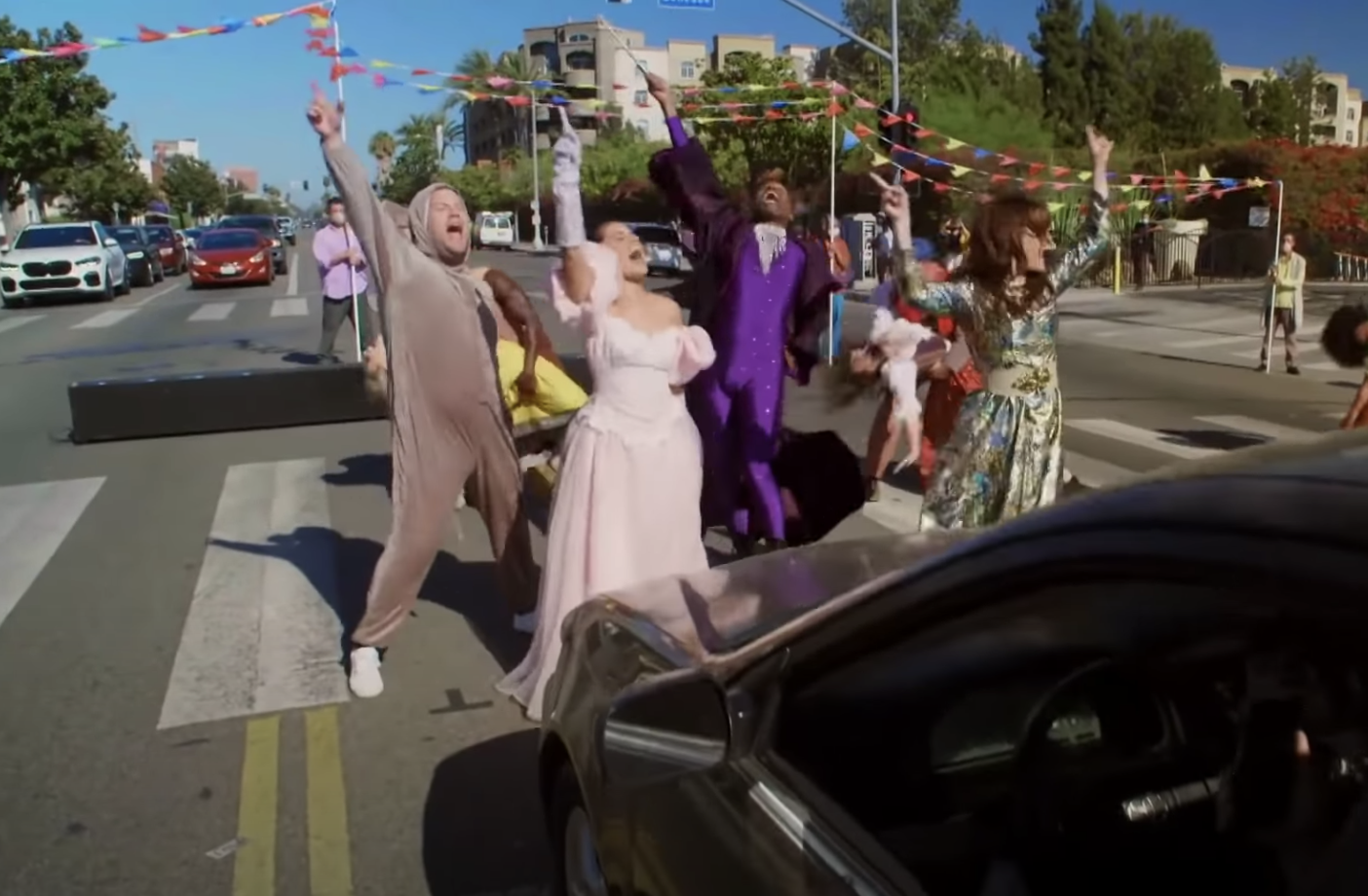 The cast performs in the crosswalk, throwing up their hands