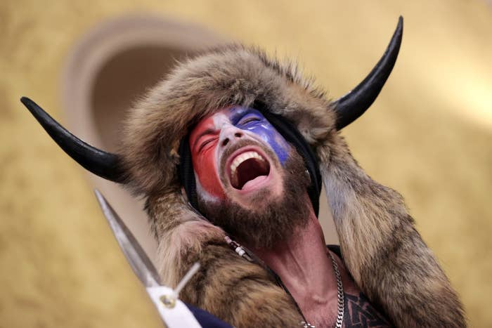 A man wearing face paint, an animal hide over his head, and horns screams