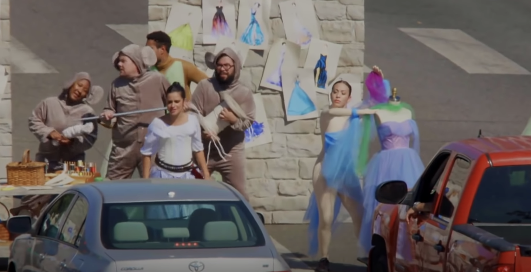 The cast performing in front of cars