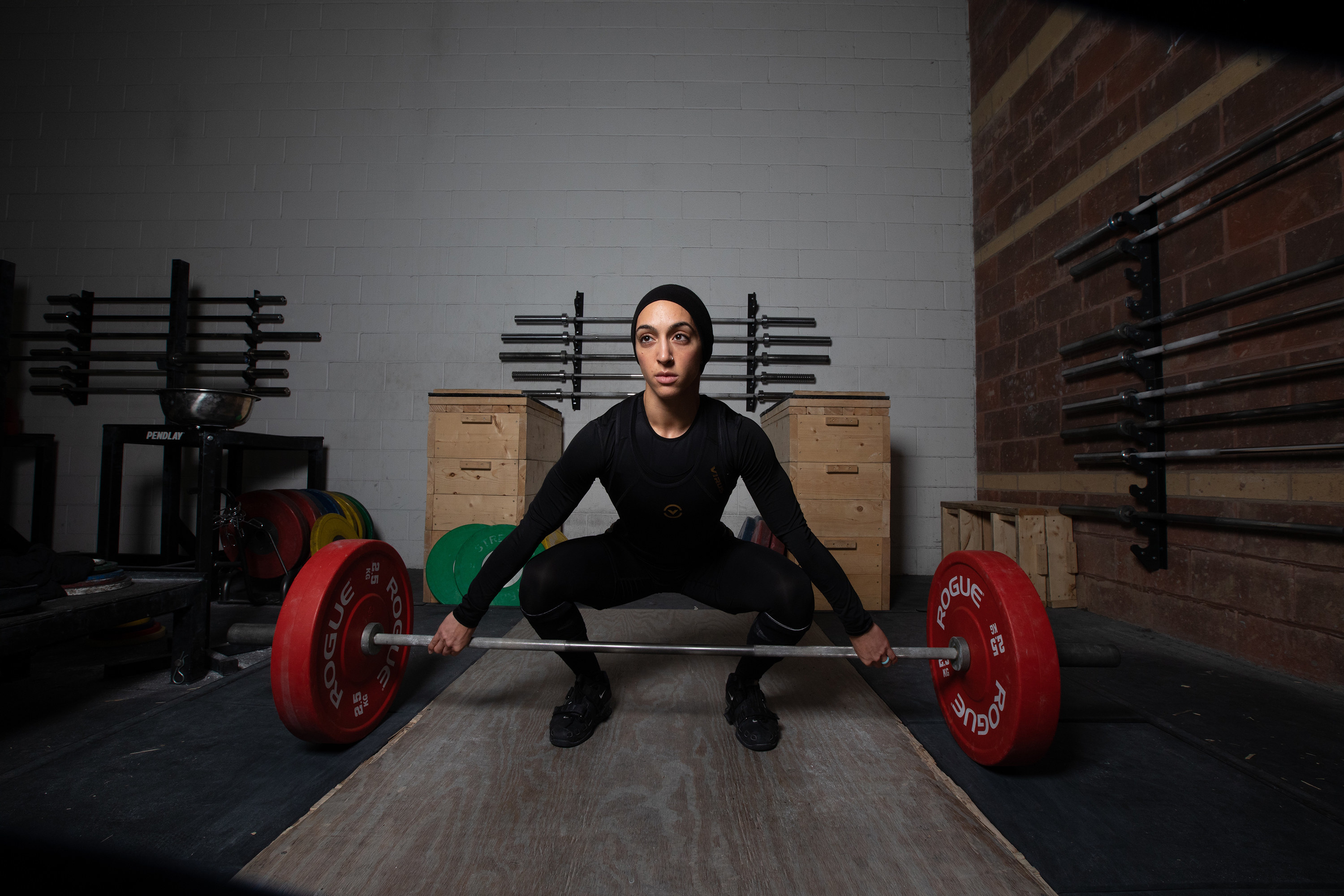 A woman with her hair covered and wearing full body workout gear lifts weights in a gym