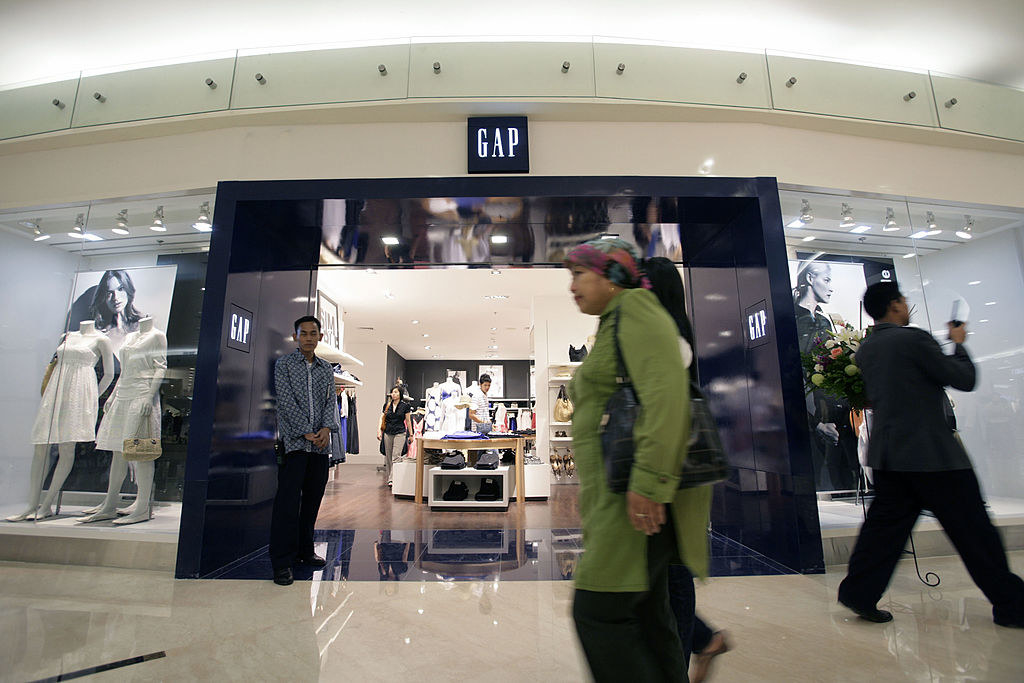 Shoppers walk by a Gap store