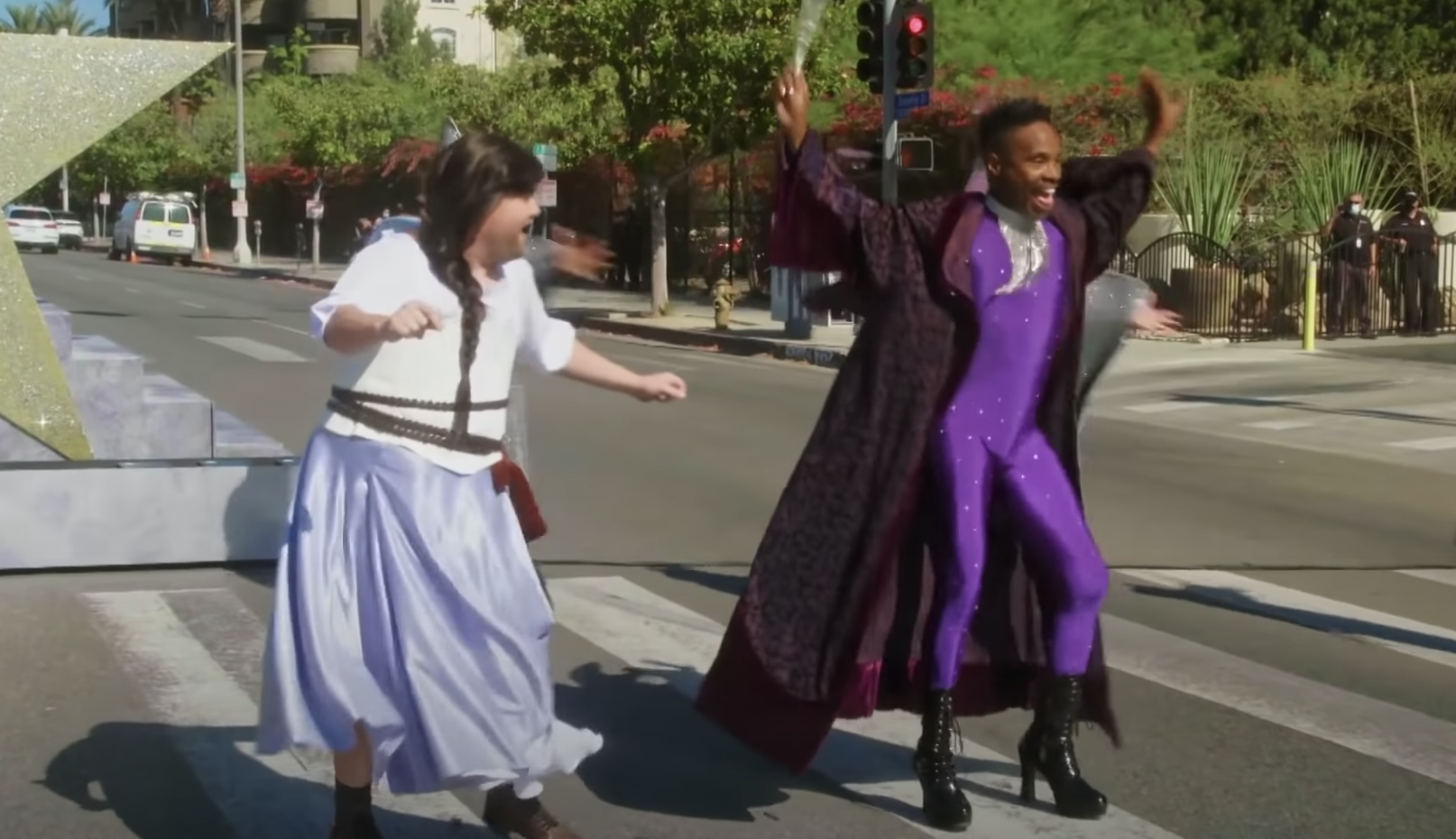 Billy dressed in a tight purple bodysuit, platform boots, and a long coat dances with James in a dress