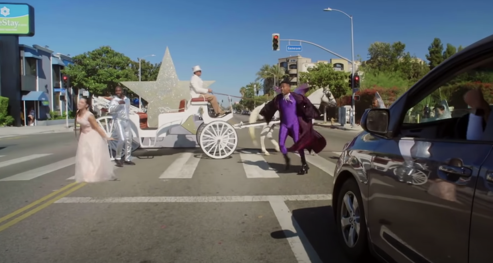 The cast standing in the crosswalk with a horse-drawn carriage in front of a car