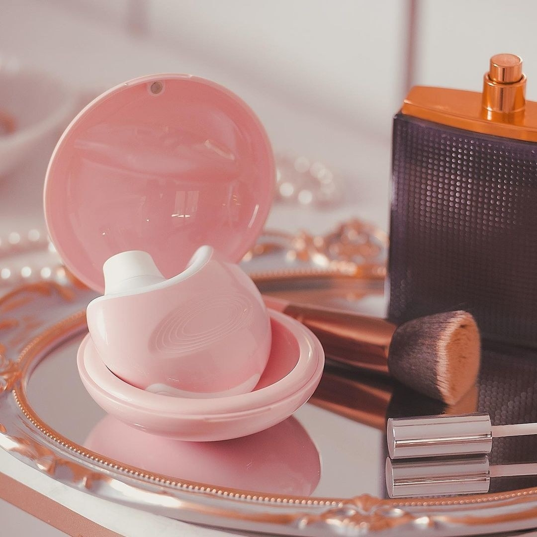 Pink suction vibrator in clamshell case on vanity