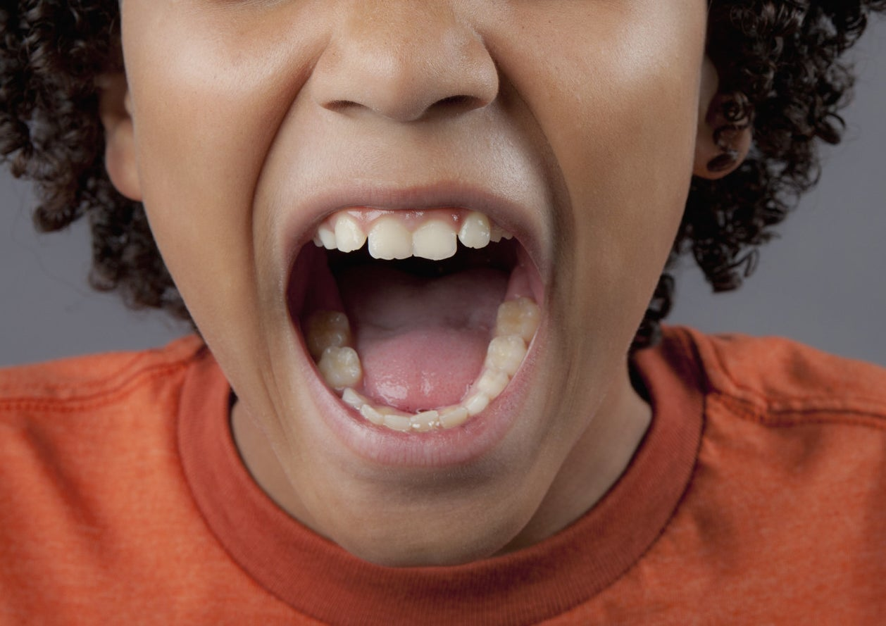 A close-up of a kid opening their mouth as if to bite something