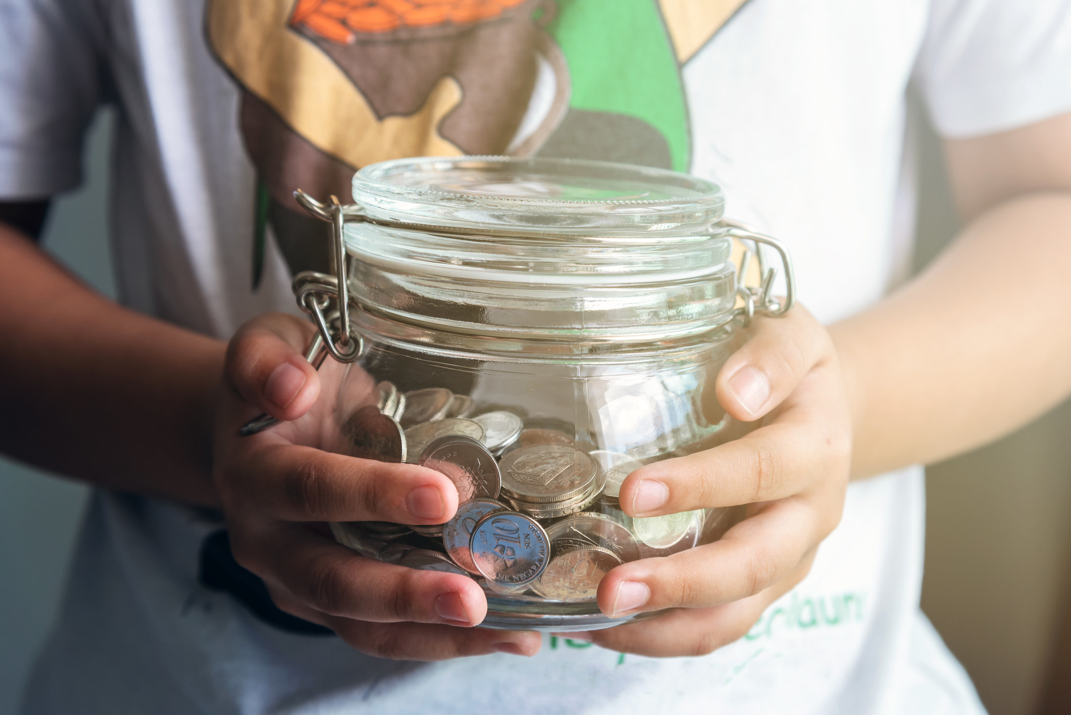 A kid holds a jar of coins