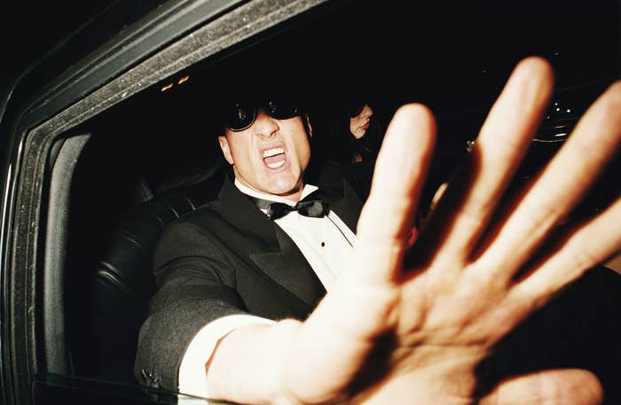 An anonymous male celebrity in a limo, yelling at a photographer