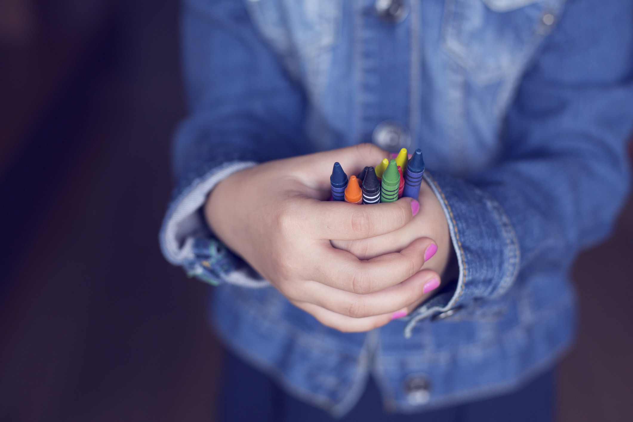 A child holds a bunch of crayons