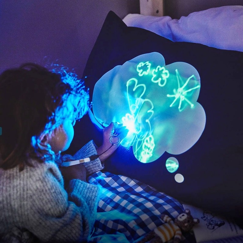 Child drawing on a glowing pillow in the dark