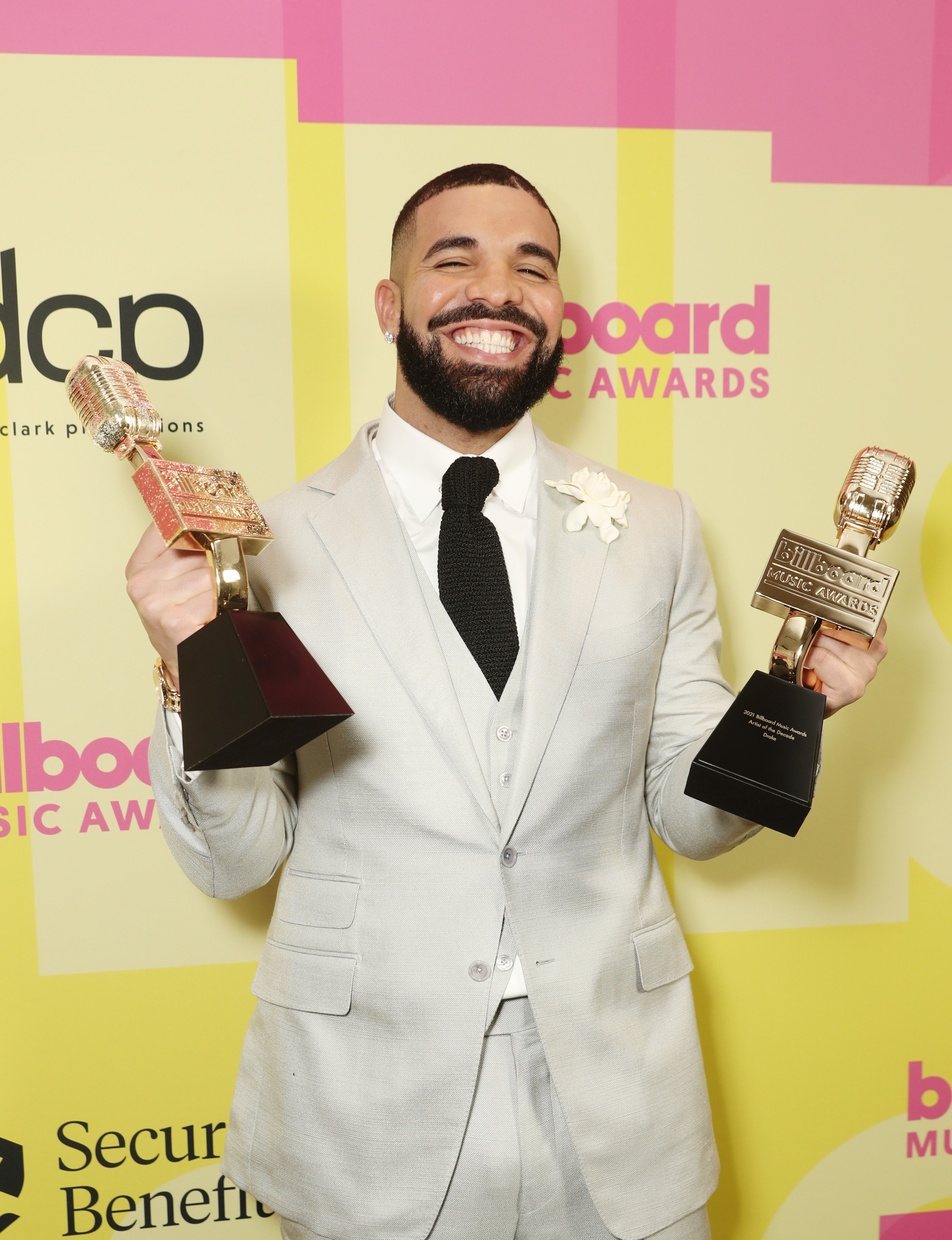 Drake smiling on the red carpet, holding up two Billboard Music Awards
