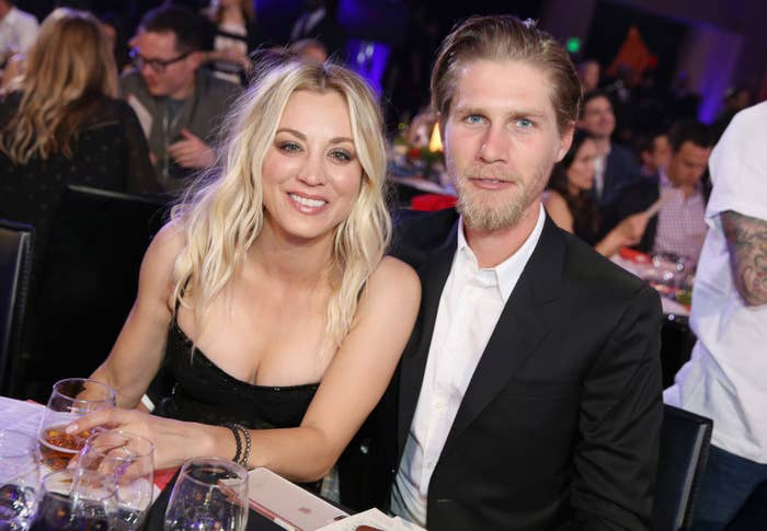 Kaley and Karl posing for a photo as they sit at a table during an awards show