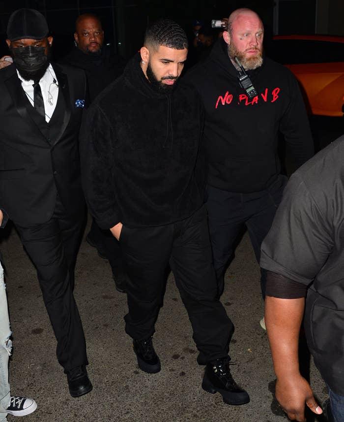 Drake walking outside surrounded by men