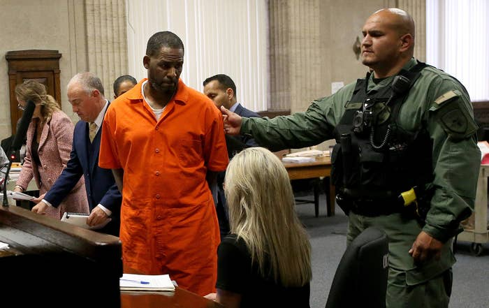 R. Kelly in an orange prison uniform and his hands behind him in a courtroom