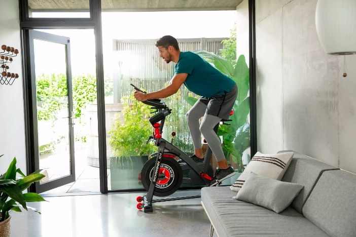 A model cycling on the exercise bike at home